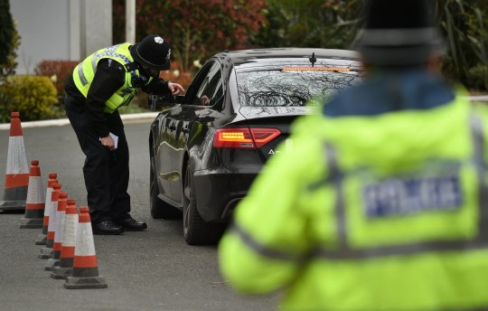 A file picture of police officers stopping motorists in cars to check that their travel is 'essential'
